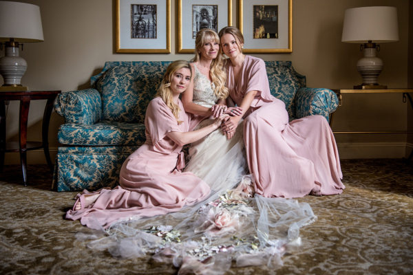 A bride and her bridesmaids pose for a photo before the wedding. Photo by The Red M Studio