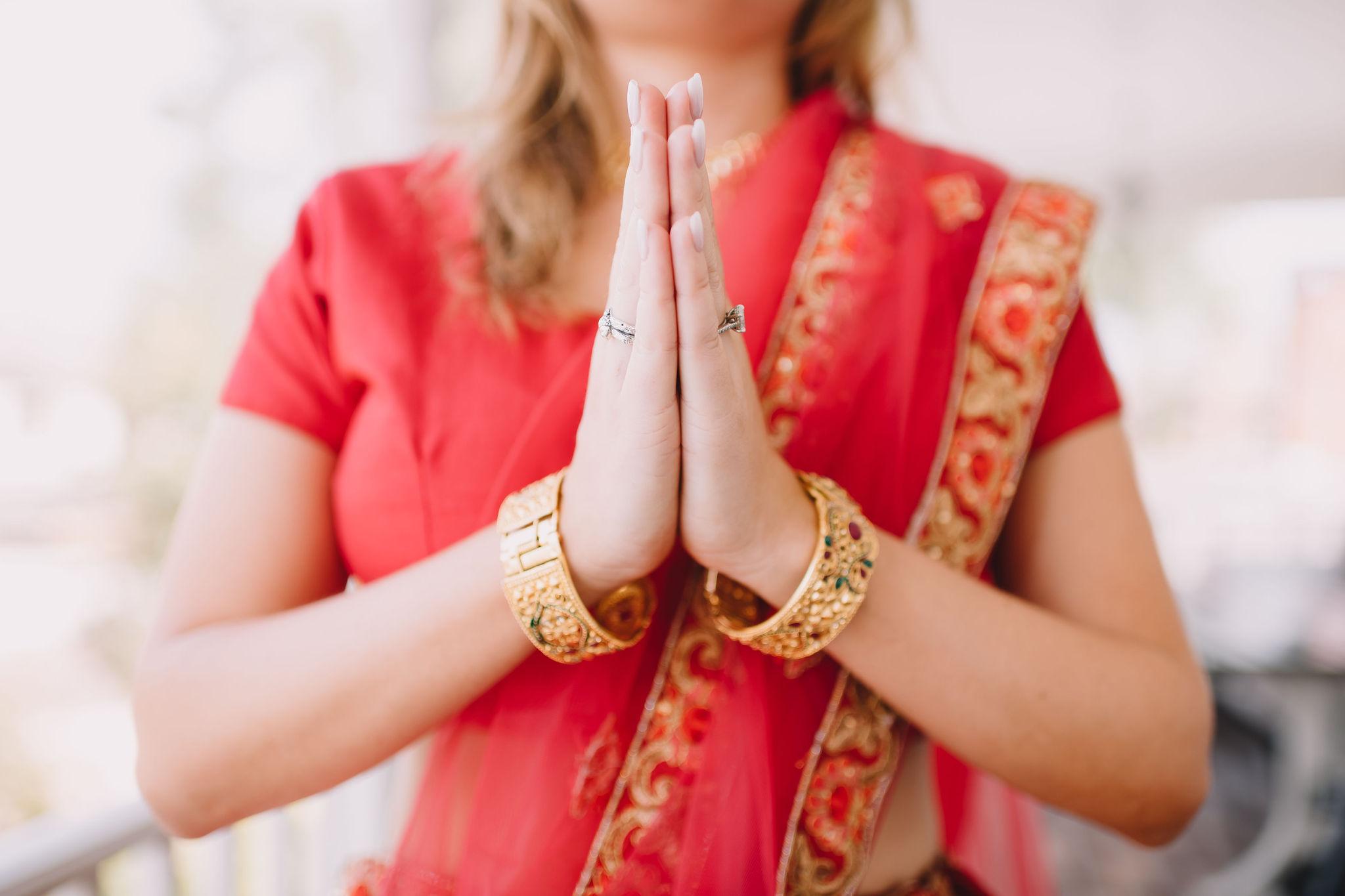 Detail of Rachel's hands in prayer pose.