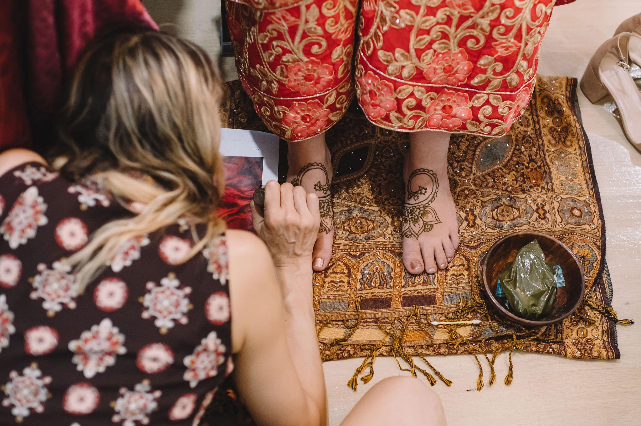 Laura Sheffield of New Orleans Henna applies Henna on Rachel's feet in intricate designs.