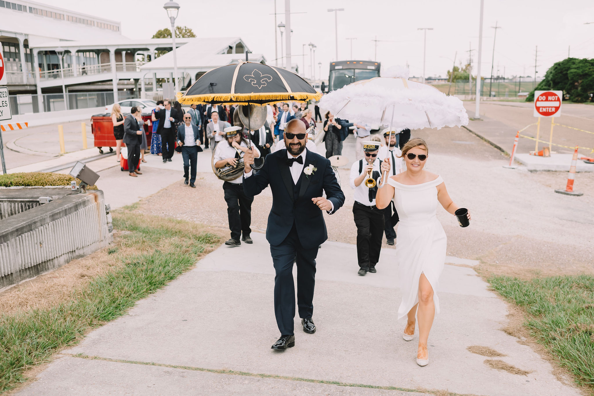 Rachel and Jimmy second line with their guests to the wedding carrying umbrellas that Rachel decorated herself.