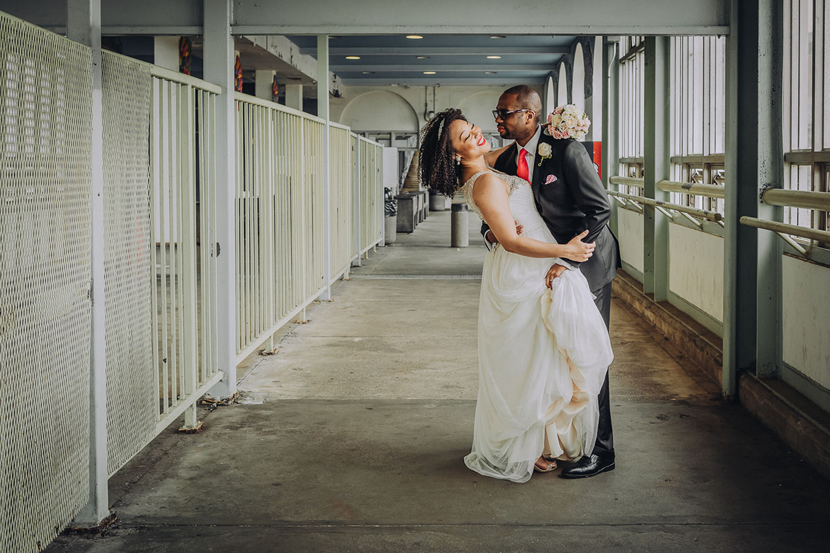 A bride and groom embrace on the boardwalk to the ferry terminal. Photo: Capture Studio Photography