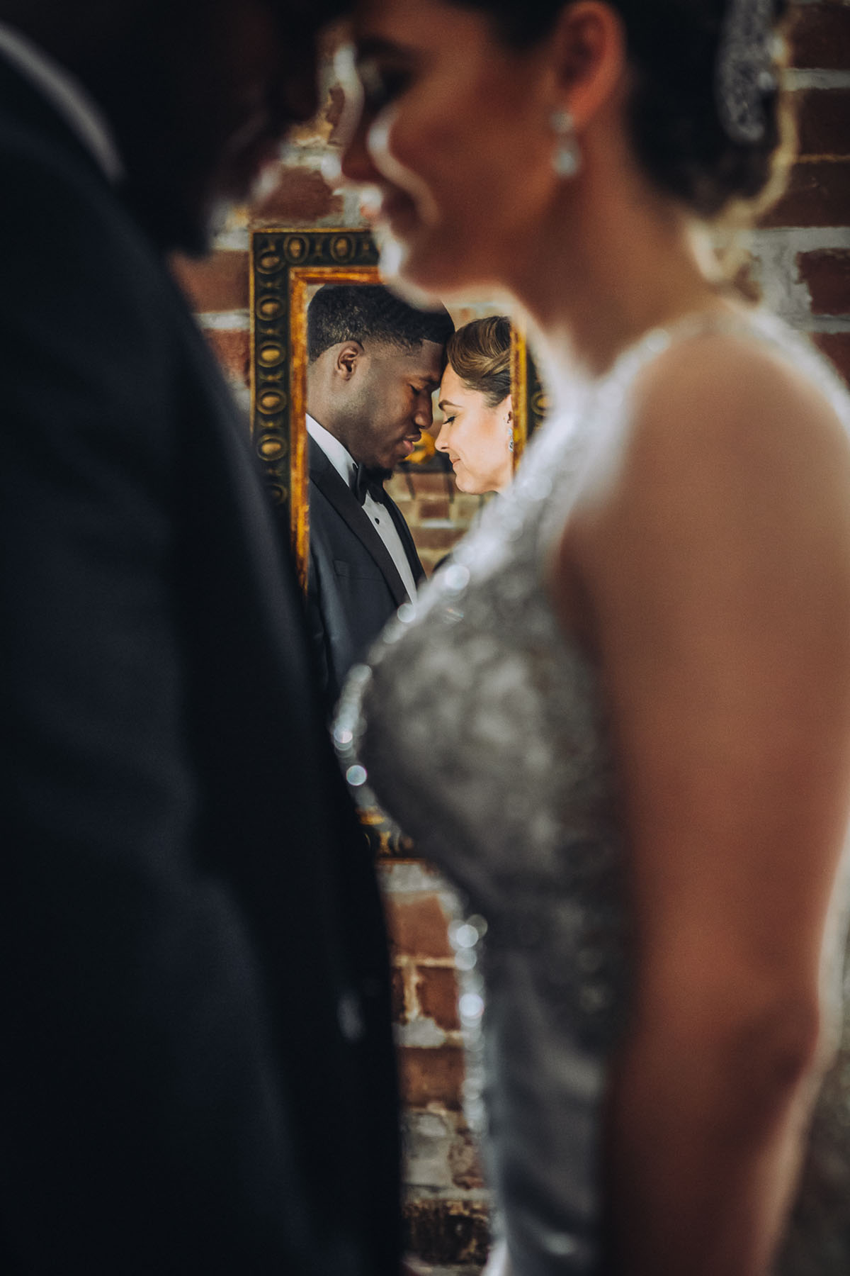 An artistic portrait of a bride and groom with a mirror reflection. Photo: Capture Studio Photography