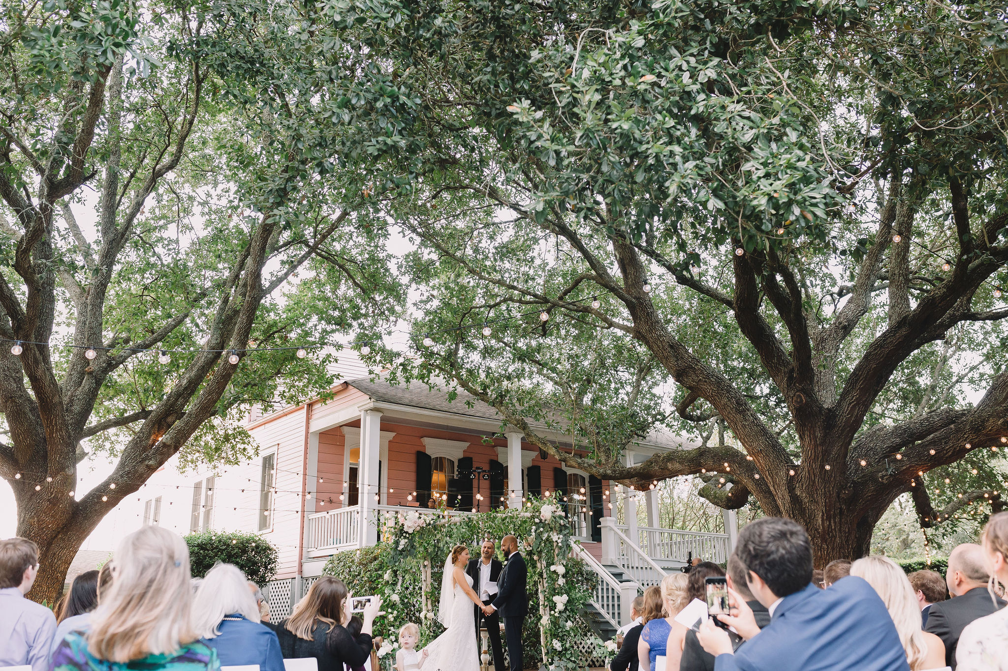 Rachel and Jimmy say their wedding vows under a mandap covered with greenery and flowers.