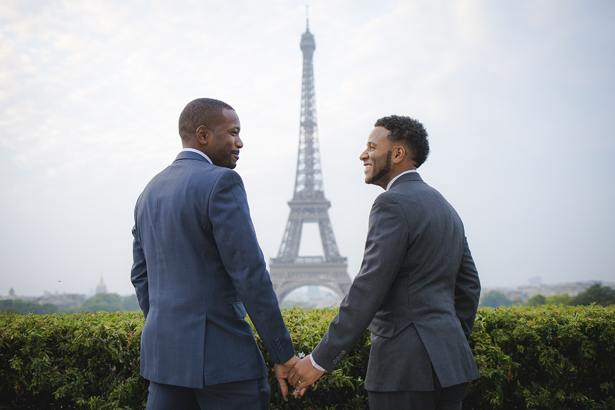 A newly engaged couple holds hands with the Eiffel Tower in the background. Photo: The Parisian Photographer