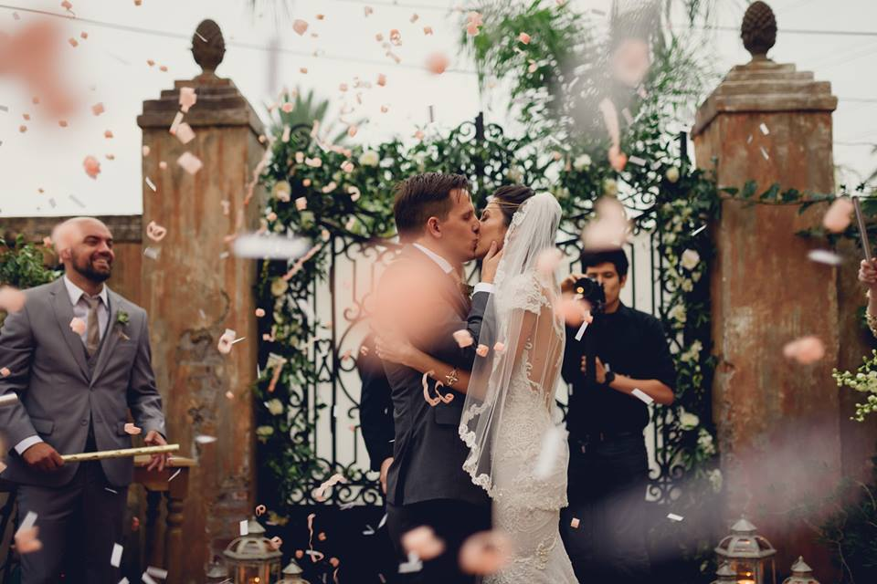 A bride and groom kiss as they are showered with rose petals. Photo: Dark Roux