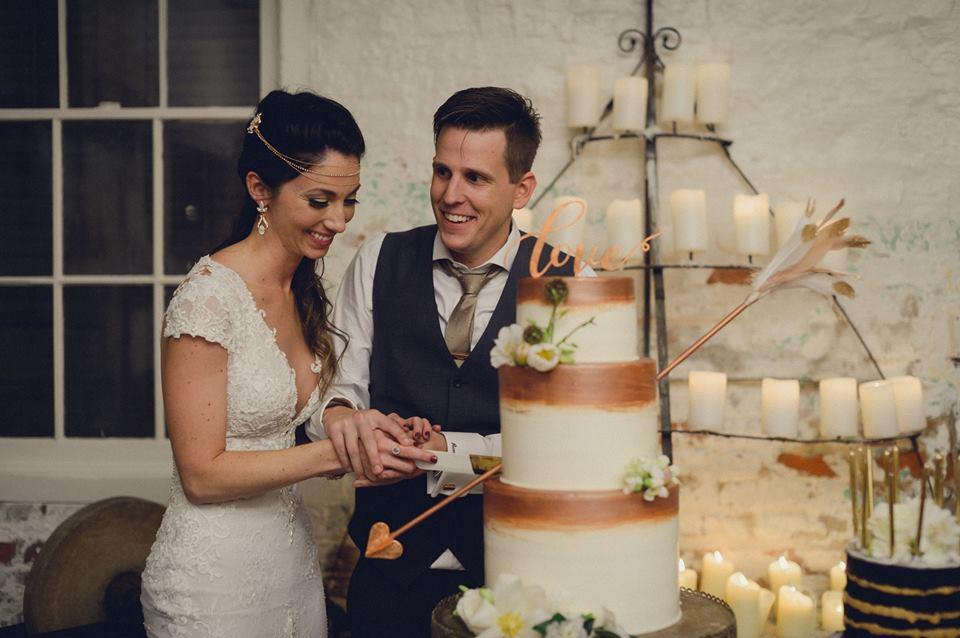 A bride and groom cut their wedding cake. Photo: Dark Roux