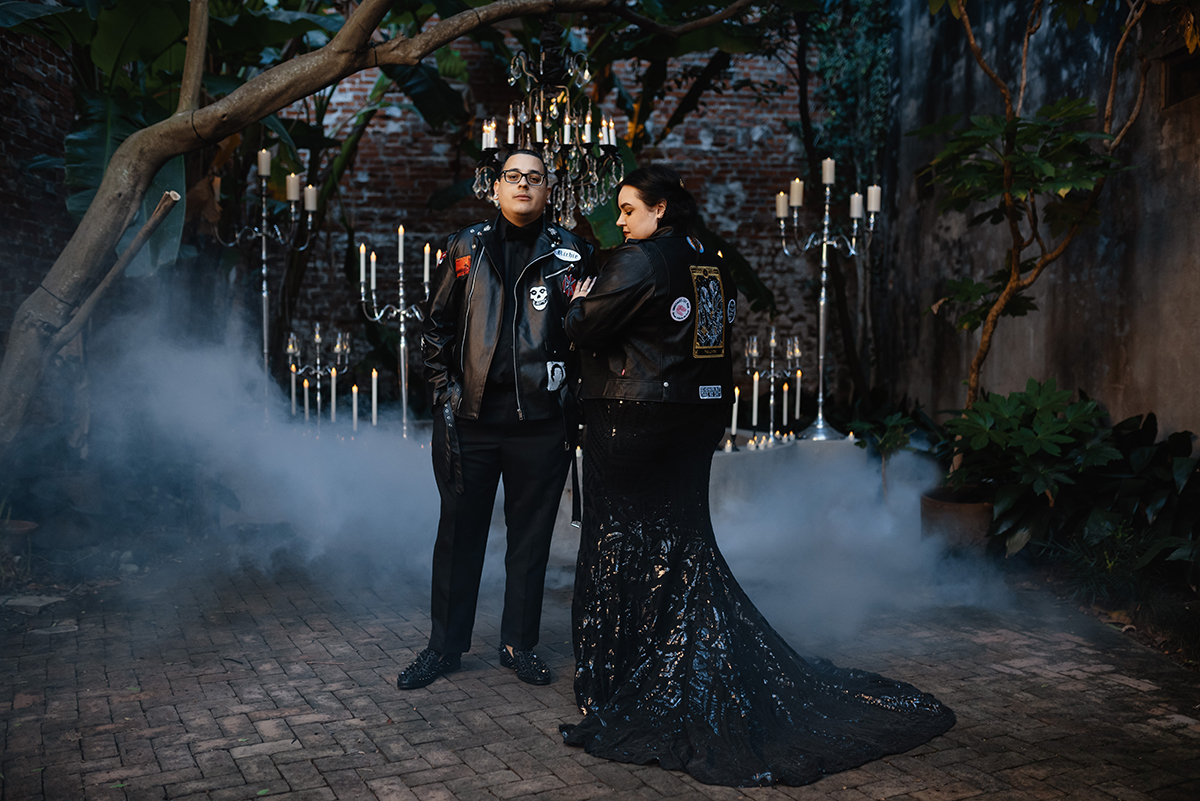 Bride and groom in all black with leather jackets in fog filled Pharmacy Museum courtyard. Photo: Dark Roux