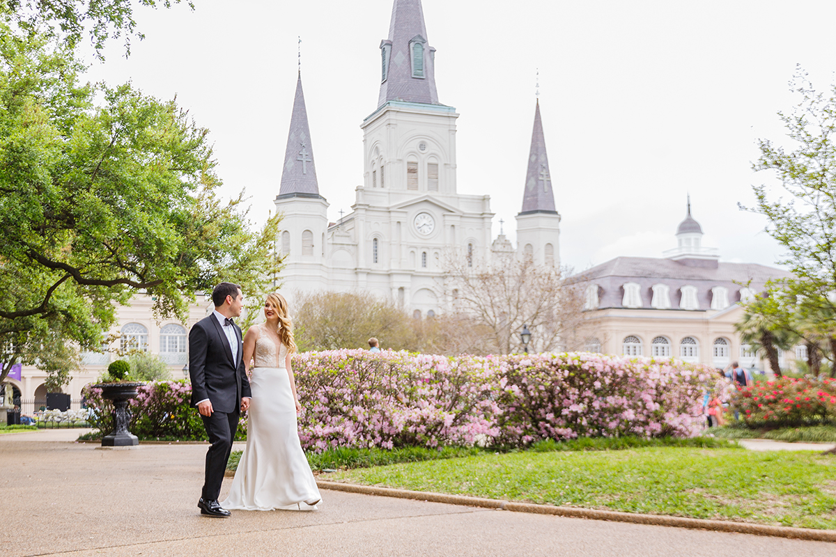 A bride and groom walk thru Jackson Square with St Louis Cathedral in the background. Photo: Studio Tran