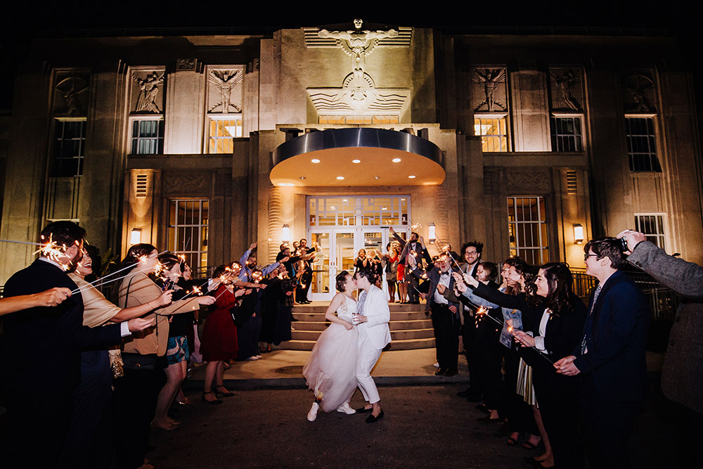 brides kissing and guests holding sparklers