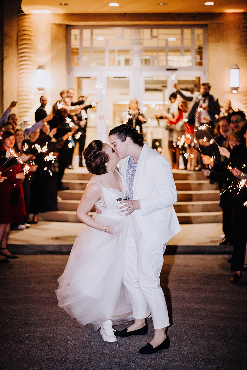 brides kissing outside between guests holding sparklers