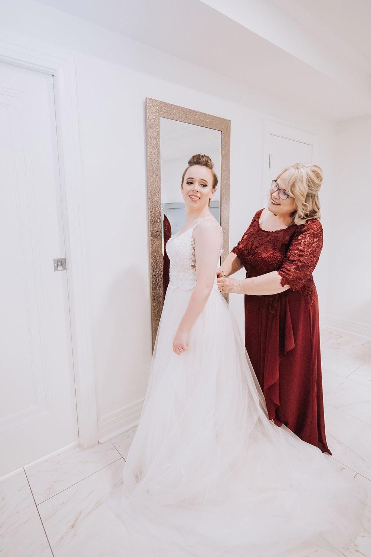 mother of bride helping bride get dressed