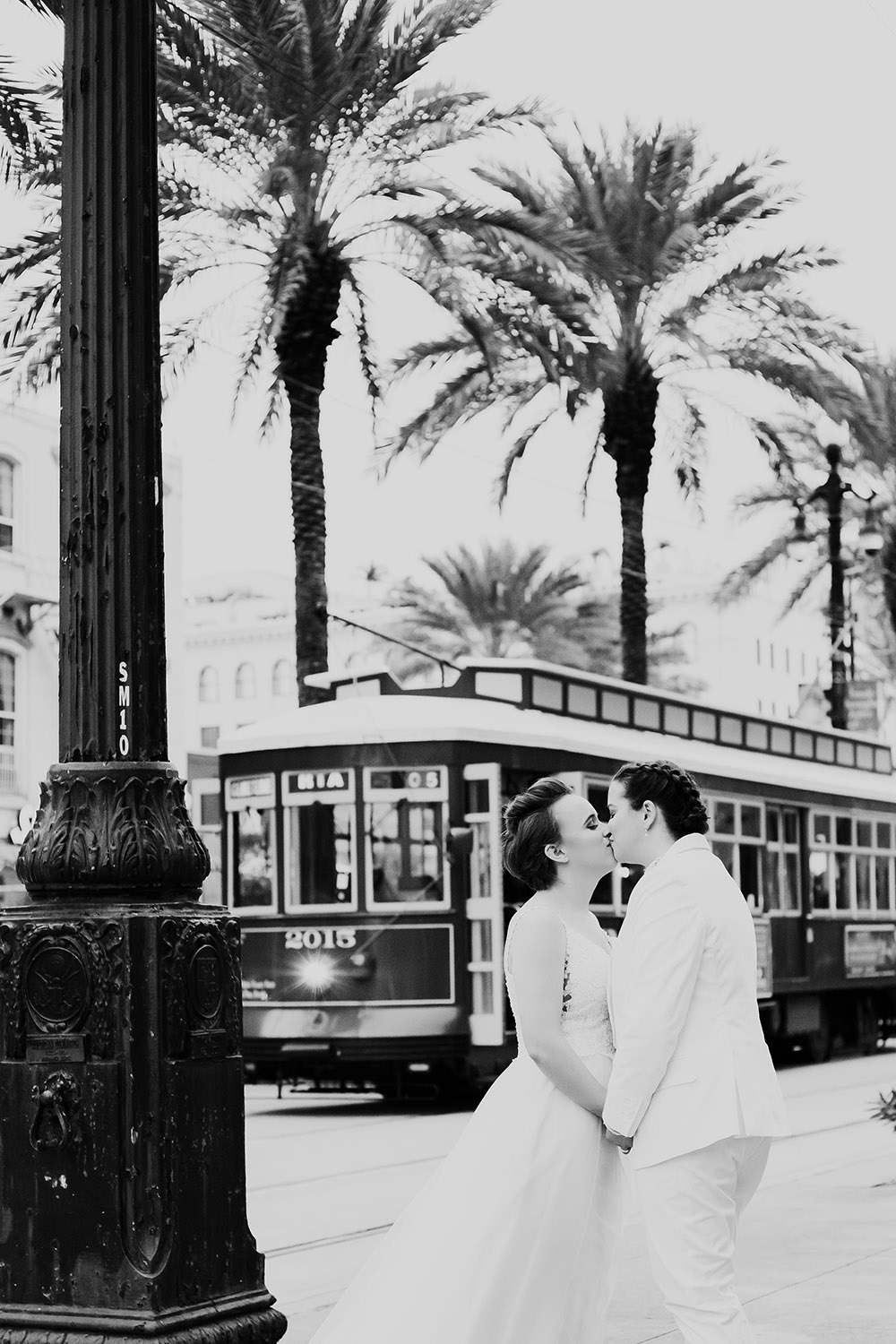 black and white photo of brides kissing new orleans streetcar