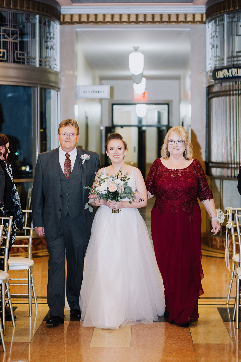 bride and parents walking up aisle
