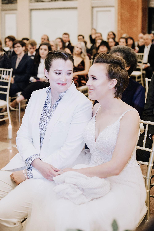 brides sitting together holding hands