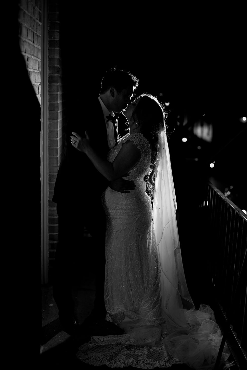 bride and groom embracing in a romantic black and white photo