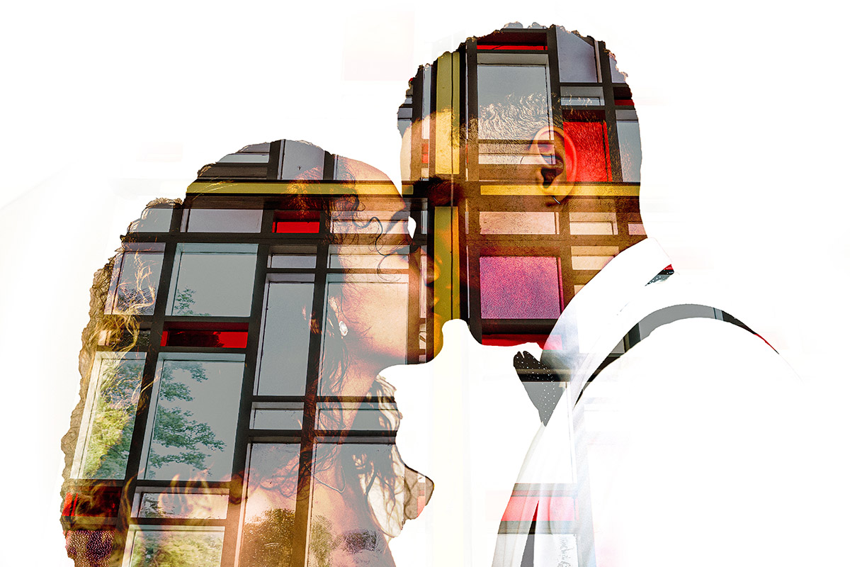 A double exposure photograph of a couple kissing with a stained glass wall by Capture Studio.