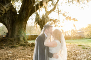 bride and groom kissing under her veil outdoor wedding