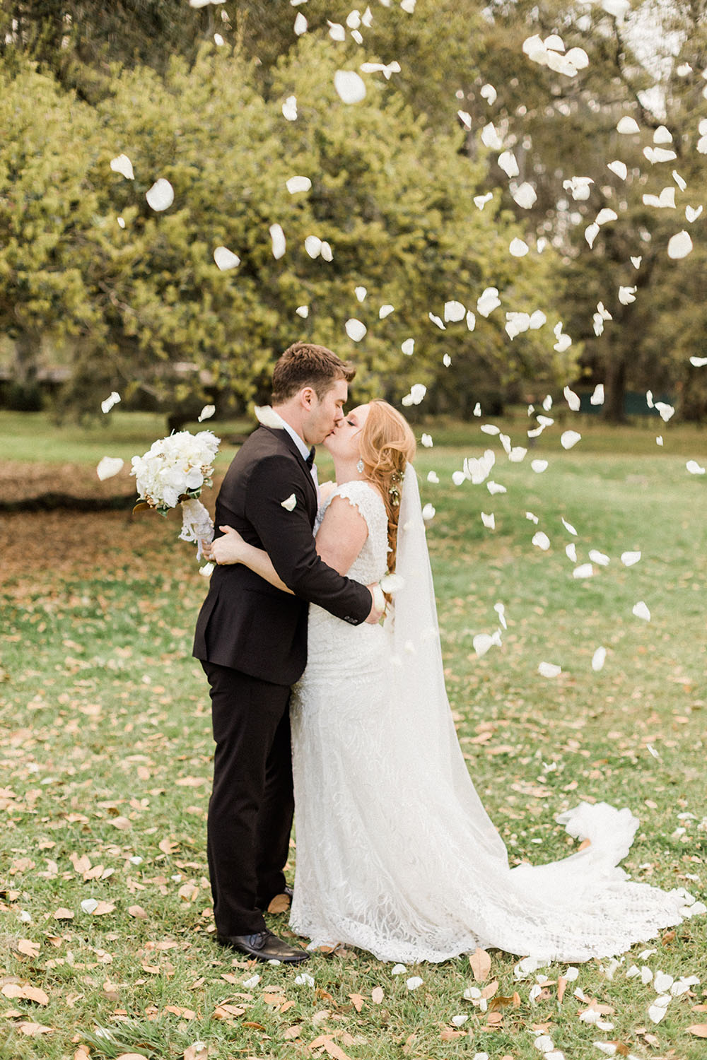 bride and groom kissing with flower petals in the air
