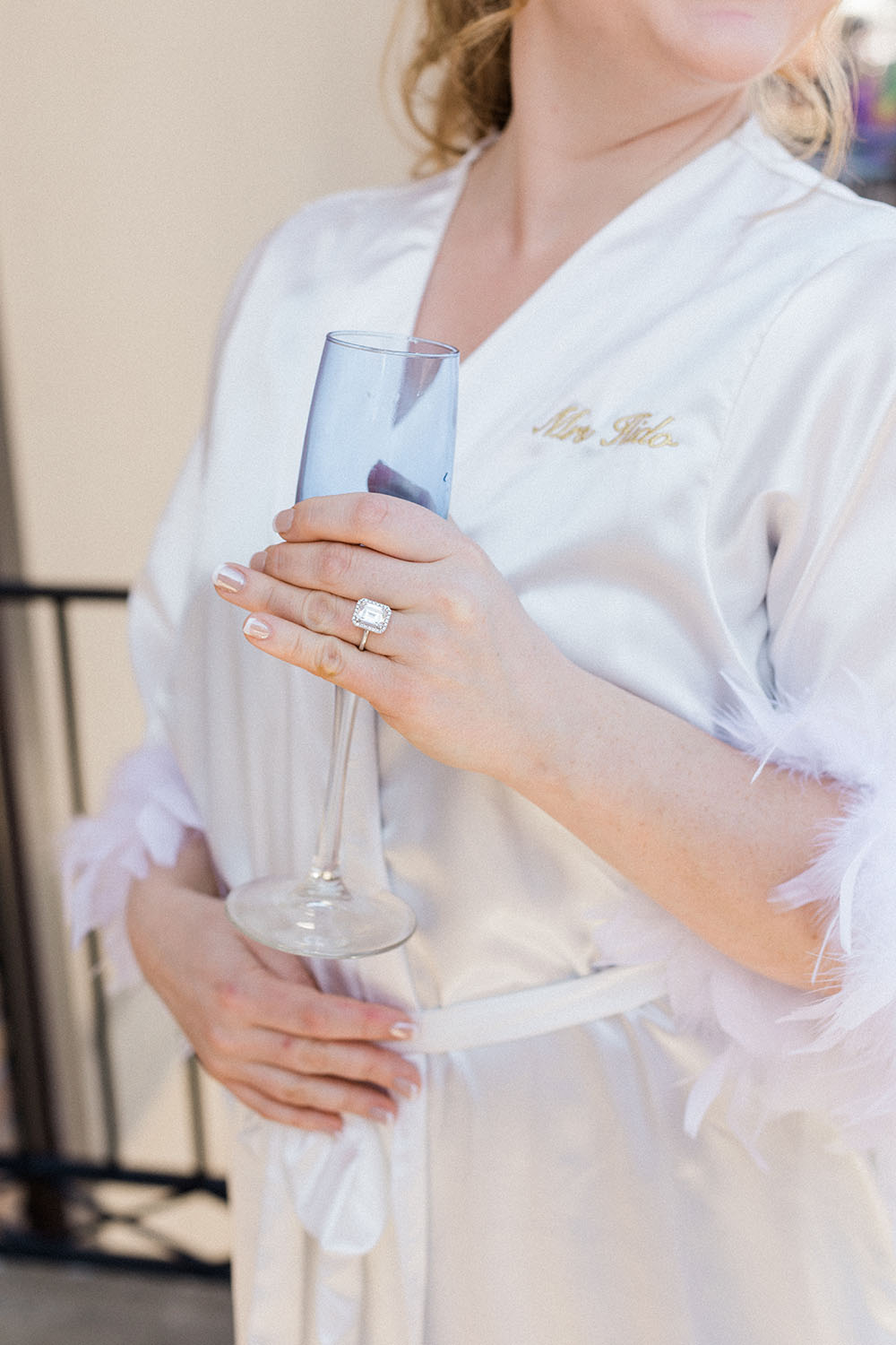 bride on the morning of her wedding day, wearing her customized robe and sipping on champagne