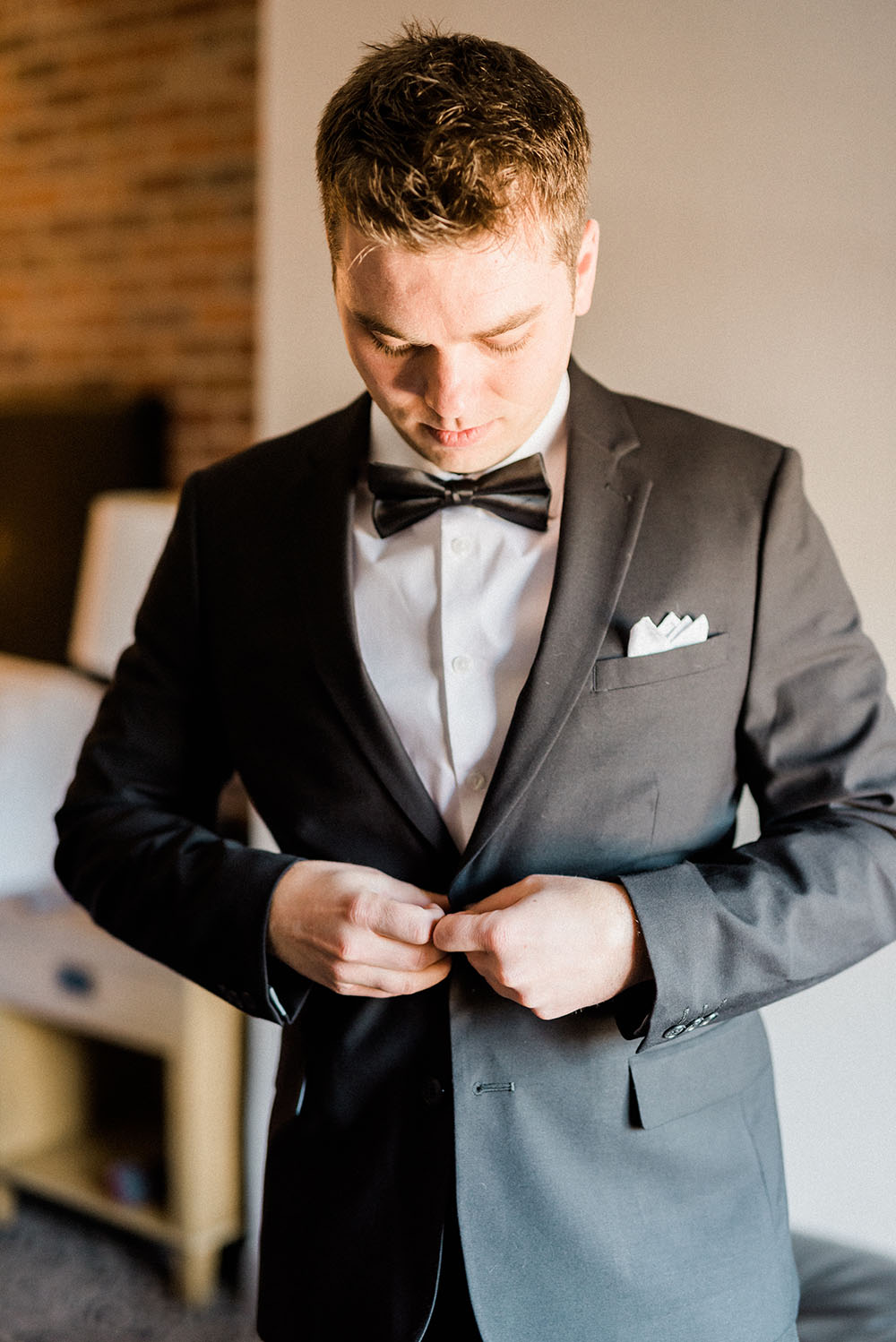 groom buttoning his jacket before wedding