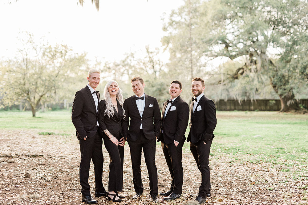 groom and friends posing before outdoor wedding ceremony