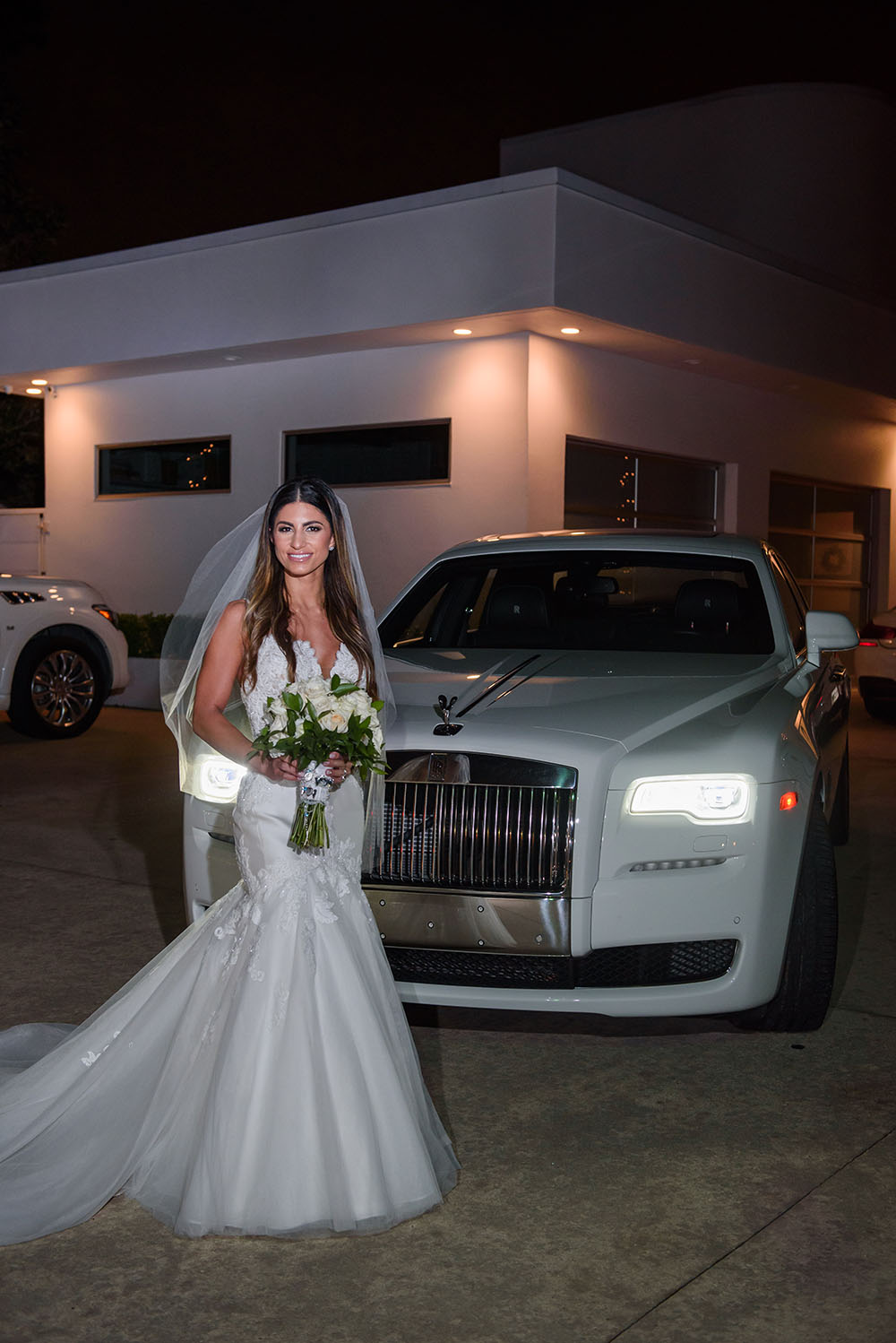 bride posing outside with the rolls royce