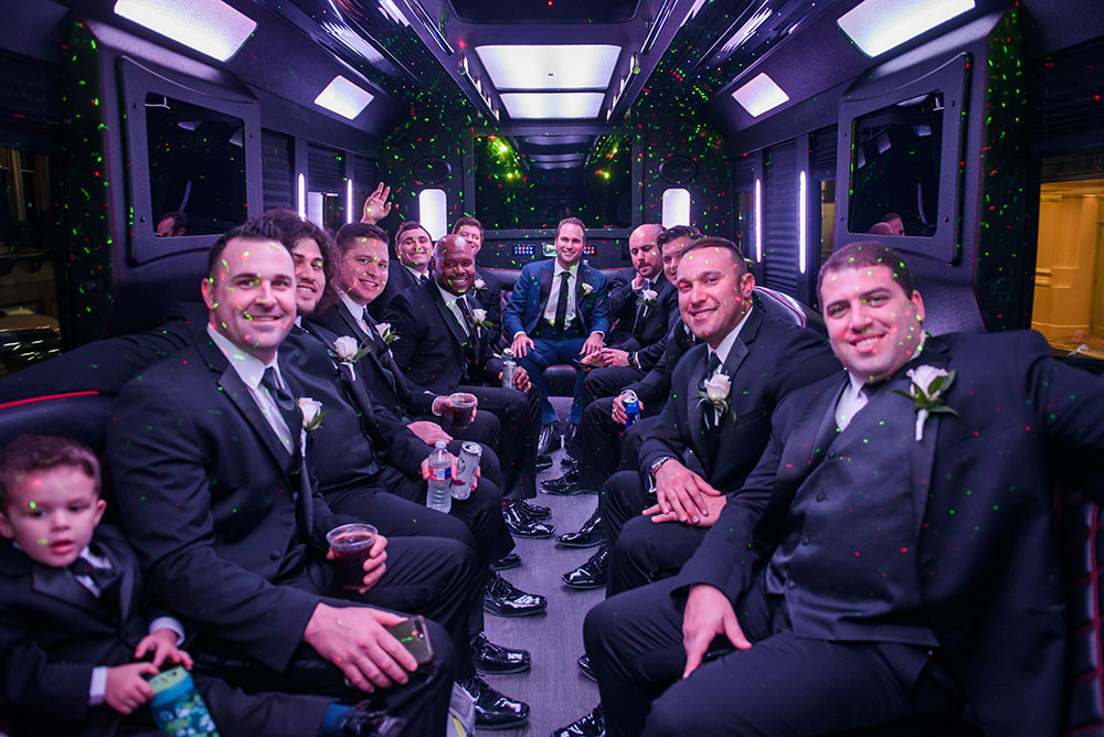 groom and groomsmen in limo bus