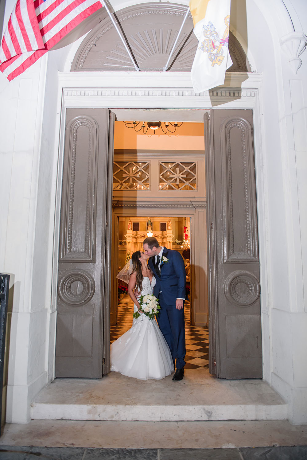 bride and groom kissing in the doorway to st. louis cathedral
