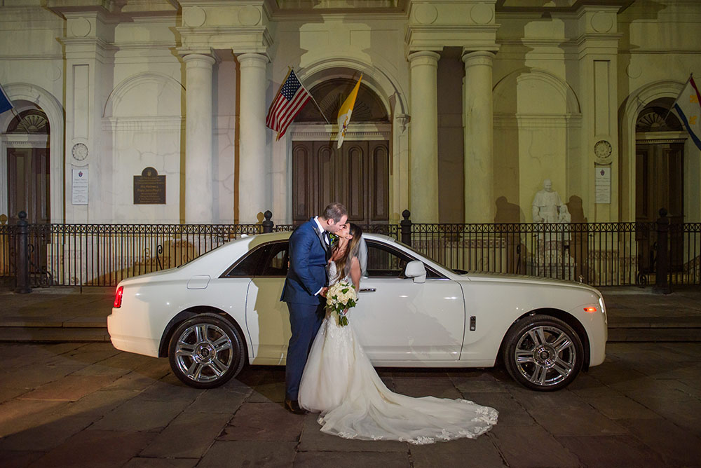 bride and groom kissing outside st. louis cathedral in front of the rolls royce