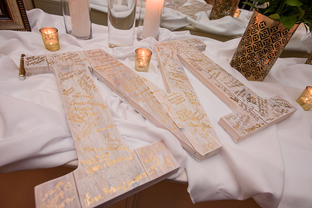 white wooden M for wedding guests to sign