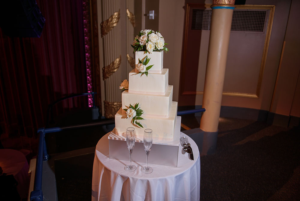 four tiered white wedding cake decorated with white roses