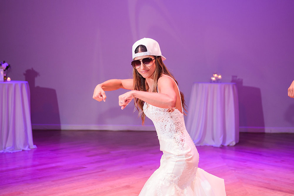 bride dancing with a backward white cap on her head