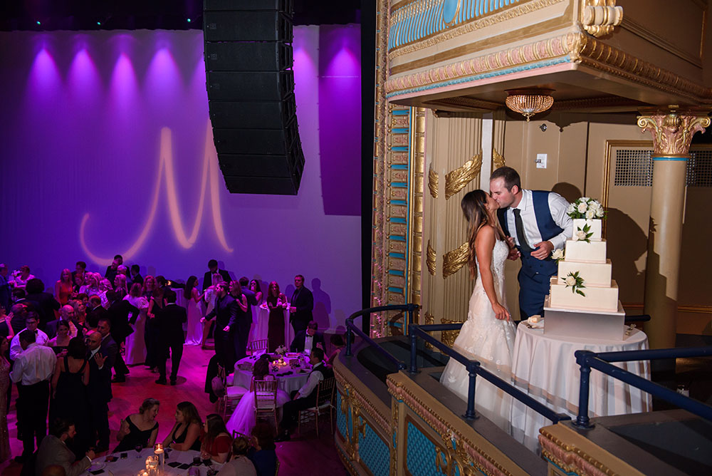 bride and groom kissing in front of wedding cake