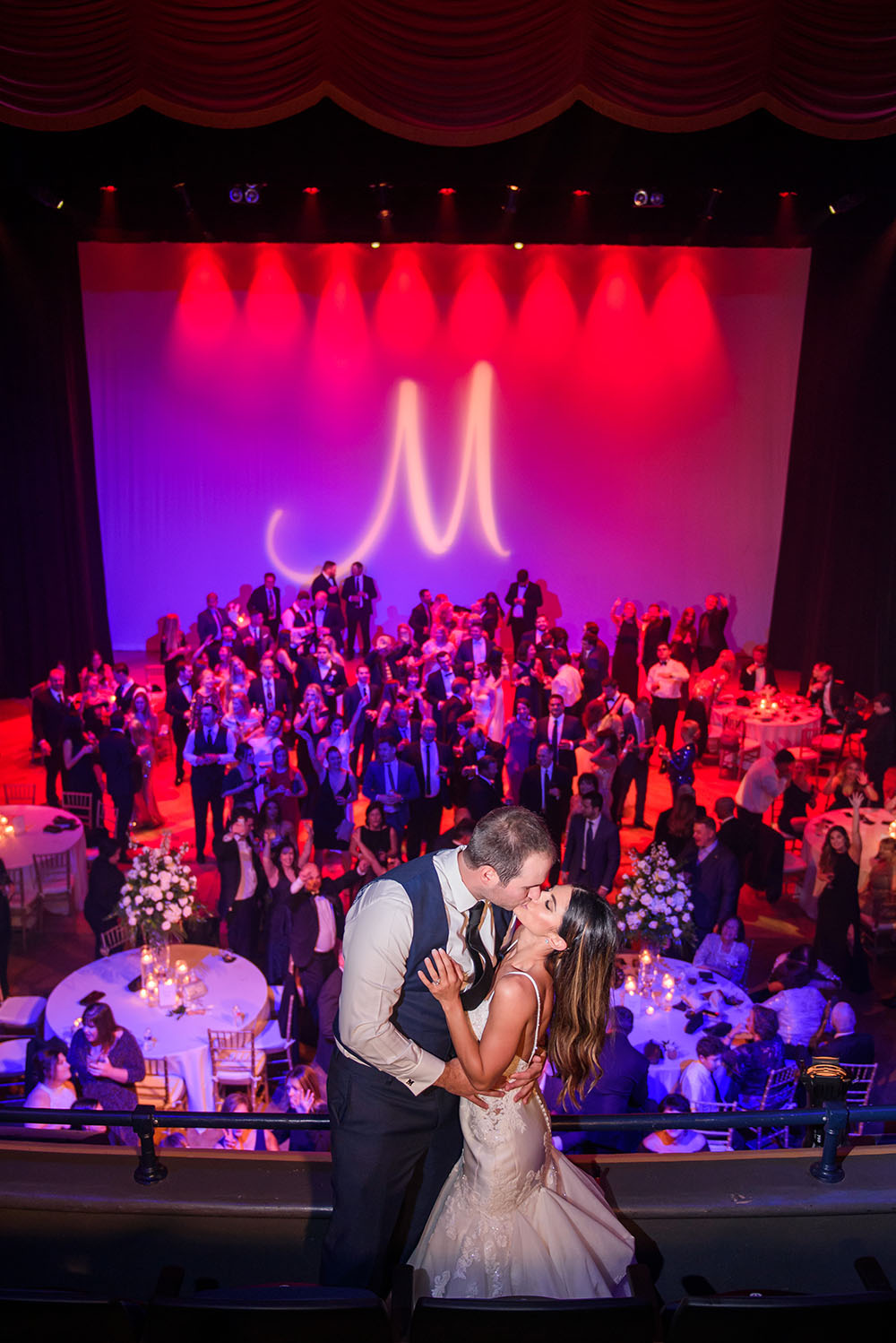 bride and groom kissing on balcony overlooking guests