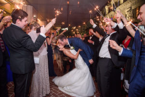 bride and groom kissing as guests wave sparklers