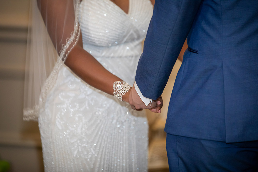 Kiara and Michael hold hands during their wedding ceremony. Photo: Brian Jarreau Photography