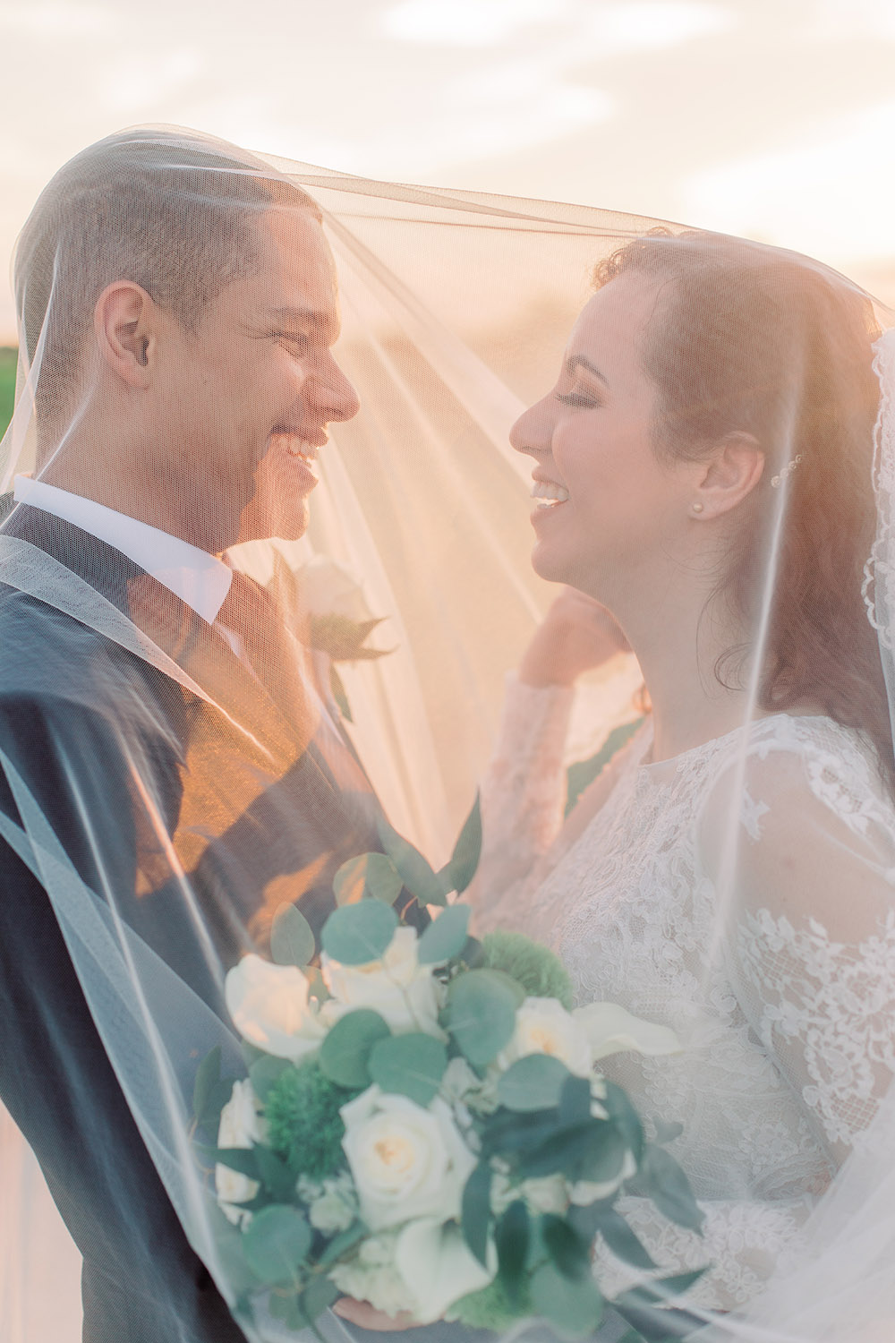 Bride and groom laugh under the bride's veil. Photo: Ashley Kristen Photography
