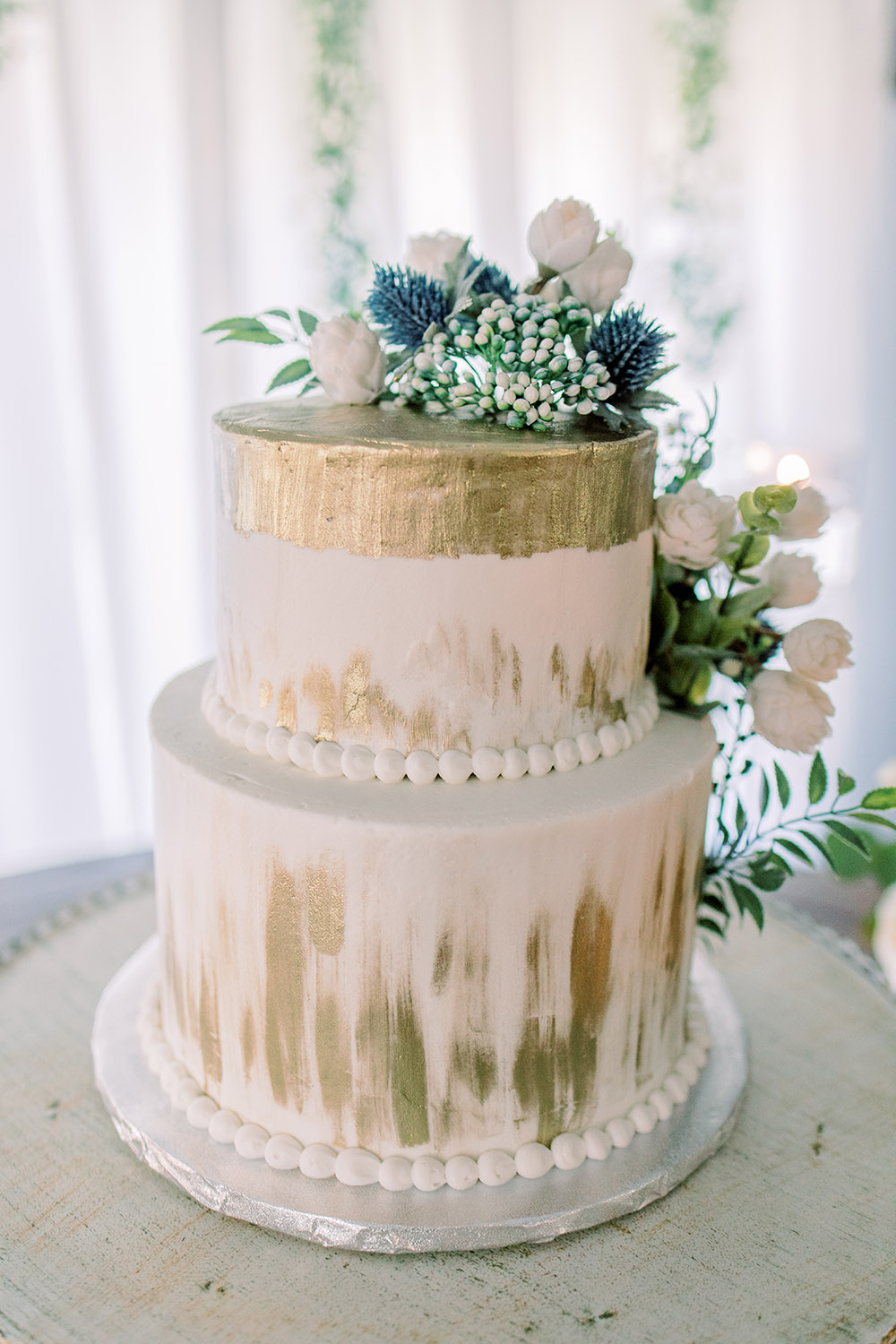 Detail of the Wedding Cake. A two-tier ivory cake with gold accents and fresh flowers and greenery. Photo: Ashley Kristen Photography