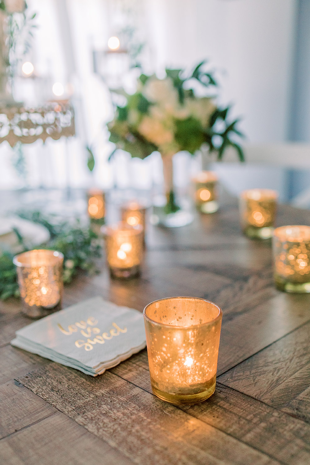 Mercury glass votives add a warm glow to the cake table. Photo: Ashley Kristen Photography
