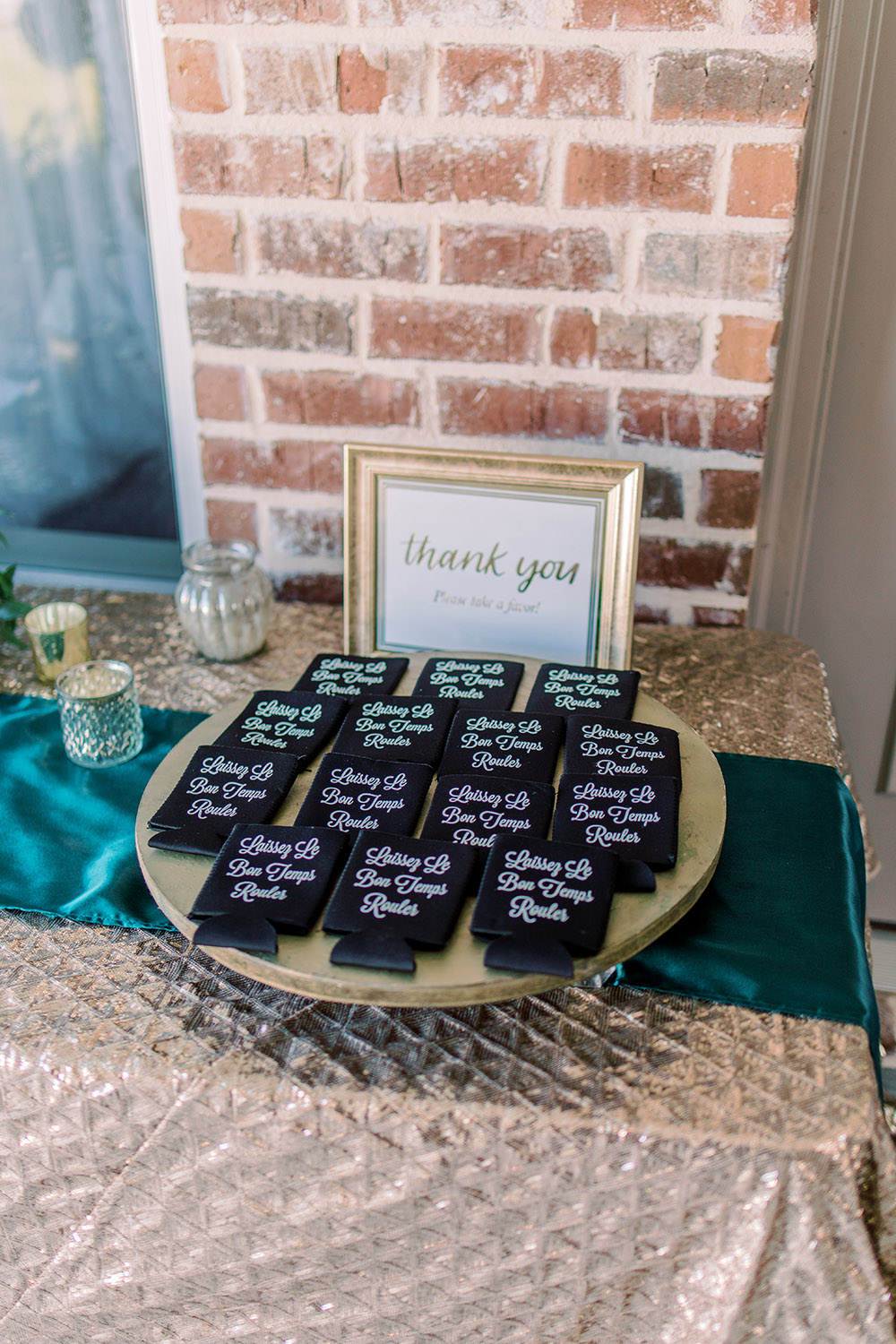 Display your favors, such as these personalized koozies that guests can use at the reception and then take home, at the entrance to the reception. Photo: Ashley Kristen Photography