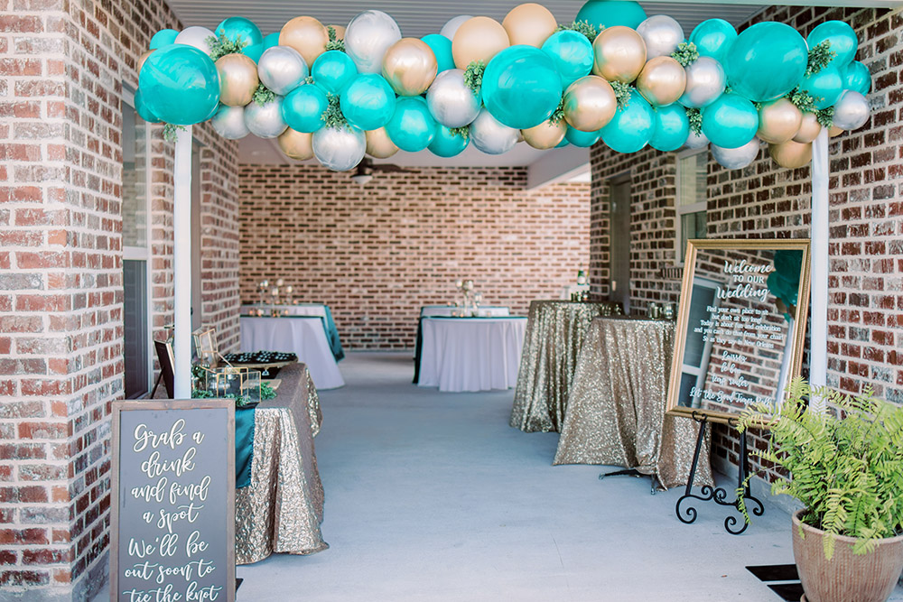 Home patio decorated for a wedding cocktail hour with emerald and gold decor. Photo: Ashley Kristen Photography