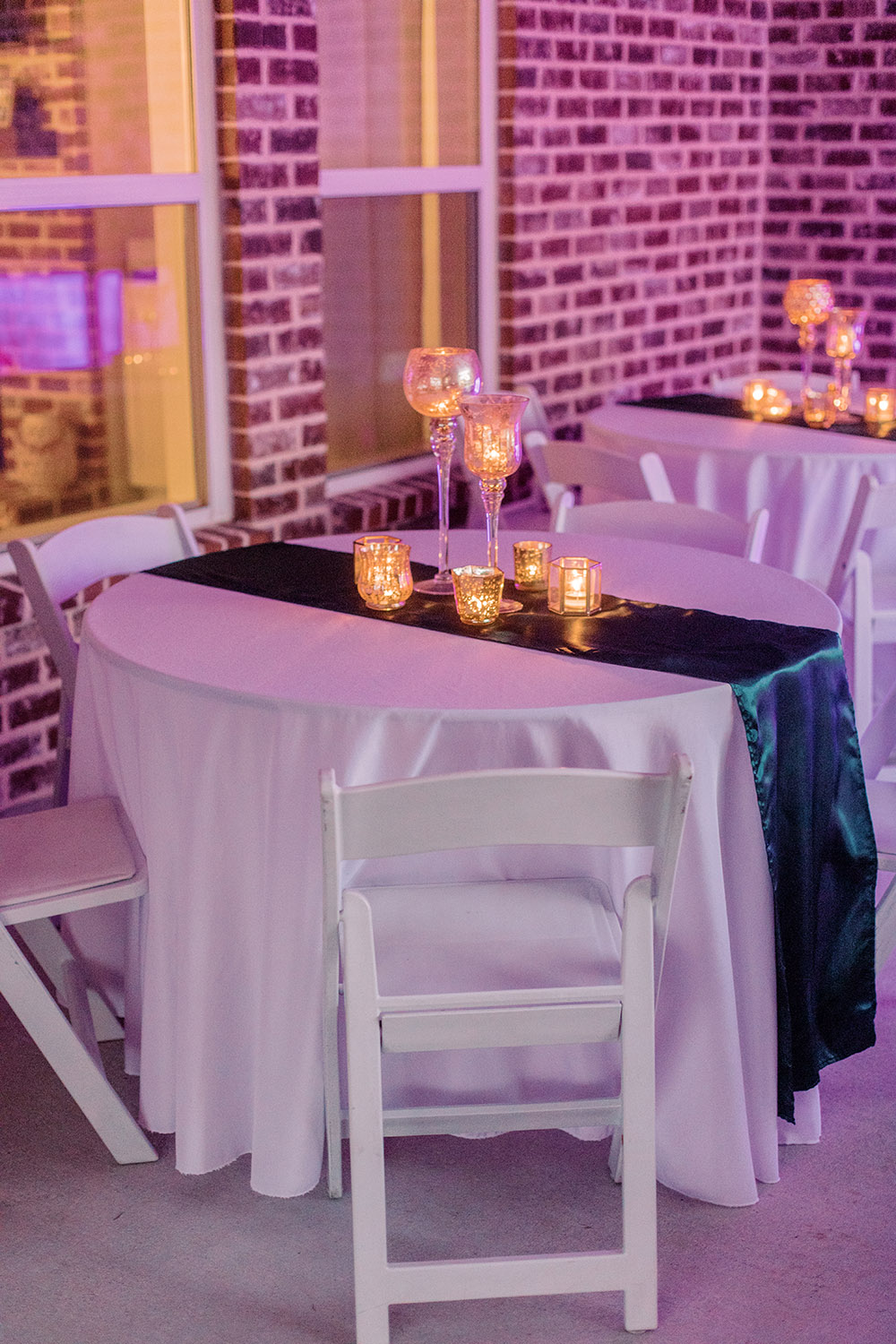 Reception tables with emerald satin runners and candles. Photo: Ashley Kristen Photography