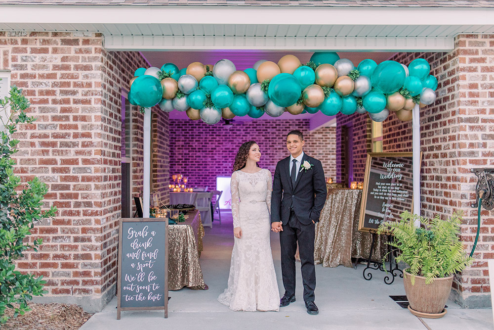 Bride and groom pose under the balloon arch entrance to the patio reception. Photo: Ashley Kristen Photography