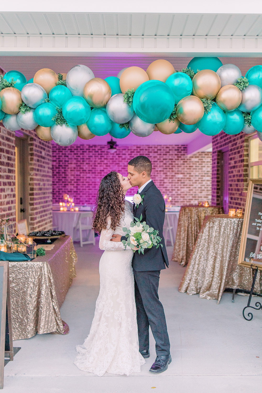 The newly wed couple embrace and kiss under the balloon arch. Photo: Ashley Kristen Photography