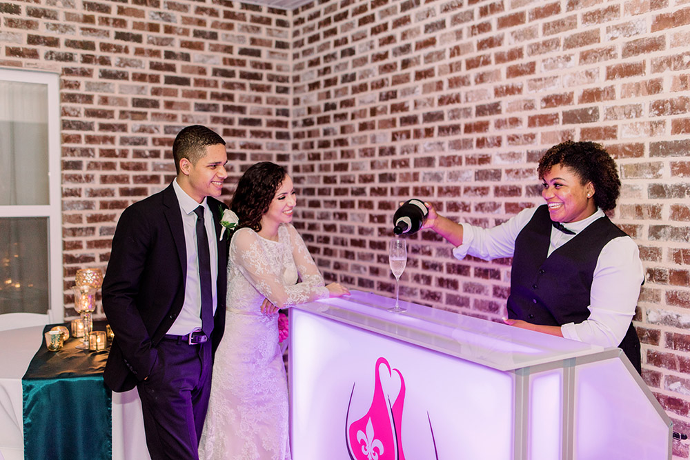 Nola Accent Bartenders serves the bride and groom a glass of champagne. Photo: Ashley Kristen Photography