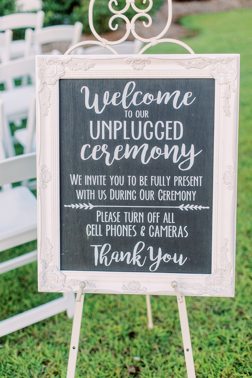 Framed chalkboard sign welcoming guests to an unplugged wedding ceremony. Photo: Ashley Kristen Photography