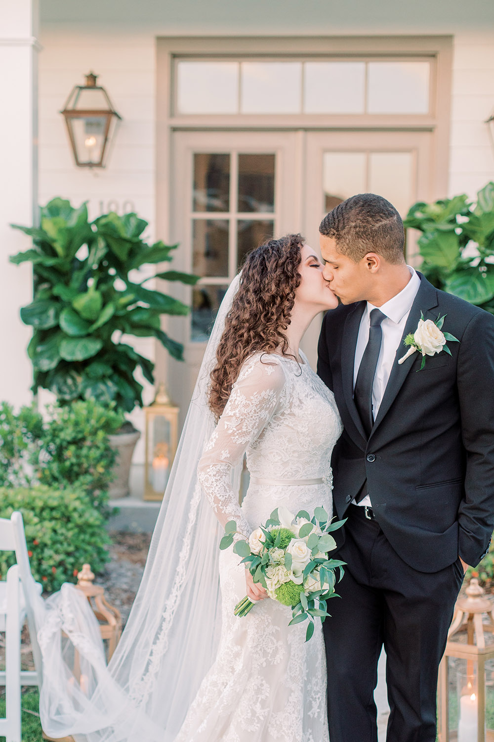 A bride and groom kiss during a front porch wedding ceremony. Photo: Ashley Kristen Photography
