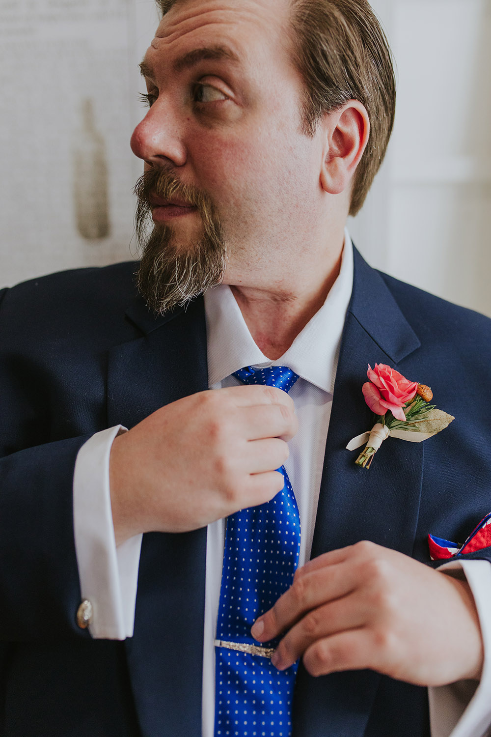 Peter looks dapper in his navy suit from British Custom Tailors. A blue tie and red and blue pocket square add a pop of color and complement his boutonniere. Photo: Ashley Biltz