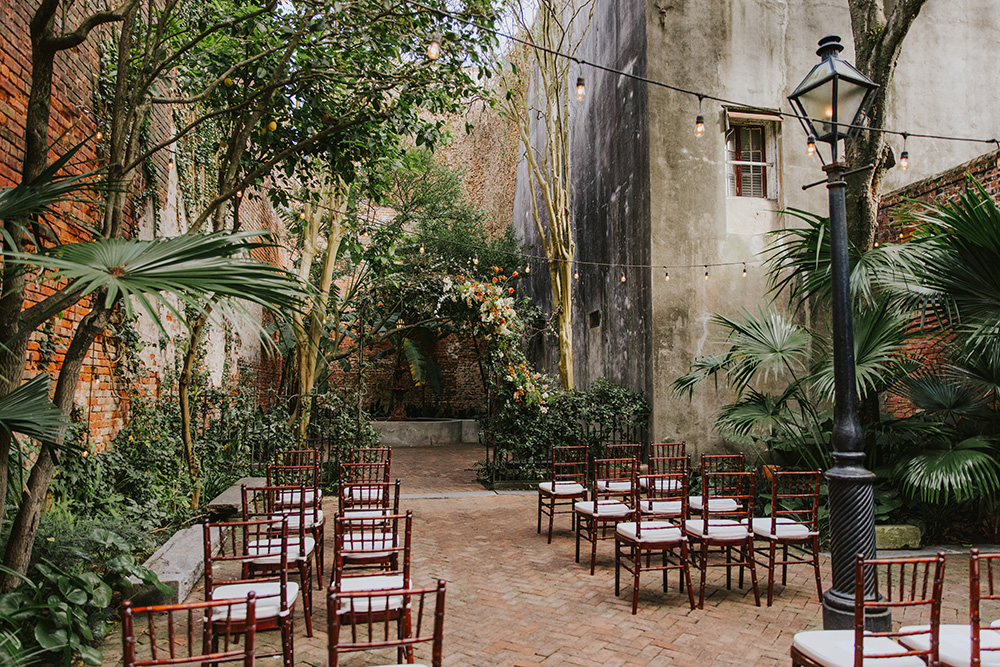The courtyard at The Pharmacy Museum set for the wedding ceremony with a floral arch and chivari chairs for the guests. Photo: Ashley Biltz