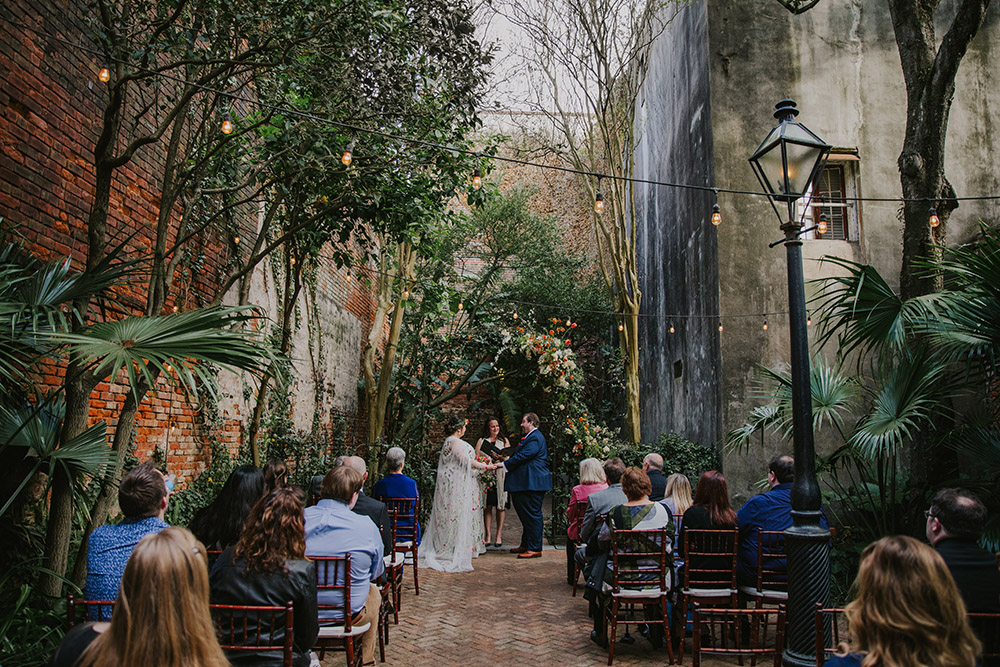 Del and Peter exchange vows under a floral arch in the Pharmacy Museum Courtyard. Photo: Ashley Biltz